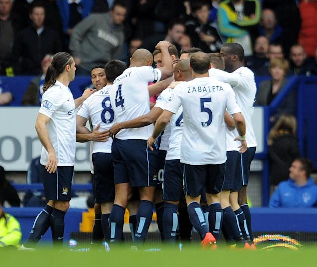 Manchester City's Edin Dzeko, center, celebrates with his teammates after he scores during their English Premier League soccer match against Everton at Goodison Park in Liverpool, England, Saturday May 3, 2014. (AP Photo/Clint Hughes)