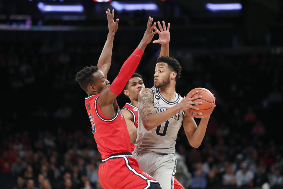 St. John's guards Rasheem Dunn, left, and Julian Champagnie, second from left, defend againstGeorgetown guard Jahvon Blair (0) during the first half of an NCAA college basketball game in the first round of the Big East men's tournament Wednesday, March 11, 2020, in New York. (AP Photo/Kathy Willens)