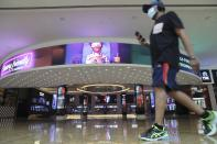 A man passes the VOX cinemas at the Mall of the Emirates in Dubai, United Arab Emirates, Thursday, April 15, 2021. The Middle East's largest operator of malls, Majid Al Futtaim, expects revenue and earnings to climb back to pre-pandemic levels by the end of next year and is moving full steam ahead with plans to develop its biggest mall ever. (AP Photo/Kamran Jebreili)