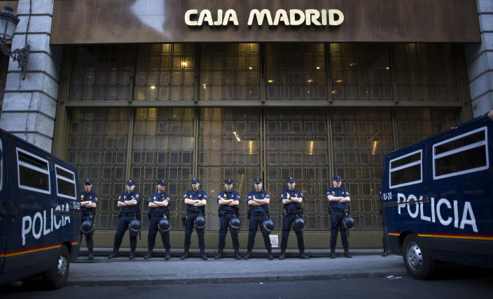 File - In this May 14, 2012 file photo, riot police stand guard in front of a branch of the recently nationalized Caja de Madrid/Bankia bank during a protest in Madrid. Spain could ask for a European rescue of its troubled banks this Saturday June 9, 2012 when European finance ministers hold an emergency conference call to discuss the nation's hurting lending sector, a move that would turn the nation into the fourth from the 17-nation eurozone to seek outside help since the continent's financial crisis erupted two years ago. (AP Photo/Alberto Di Lolli, File)