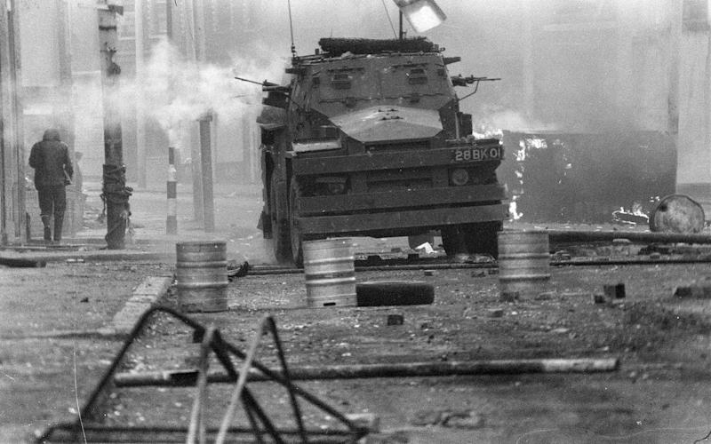A British Army armoured vehicle makes its way along a barricade while on patrol in the Lower Falls area of west Belfast during The Troubles - Credit: AP Photo/Michel Lipchitz