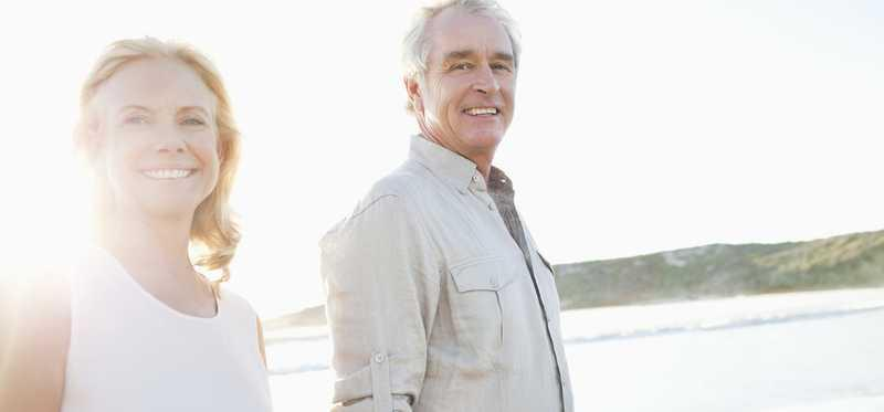 An elderly couple walks on a beach.
