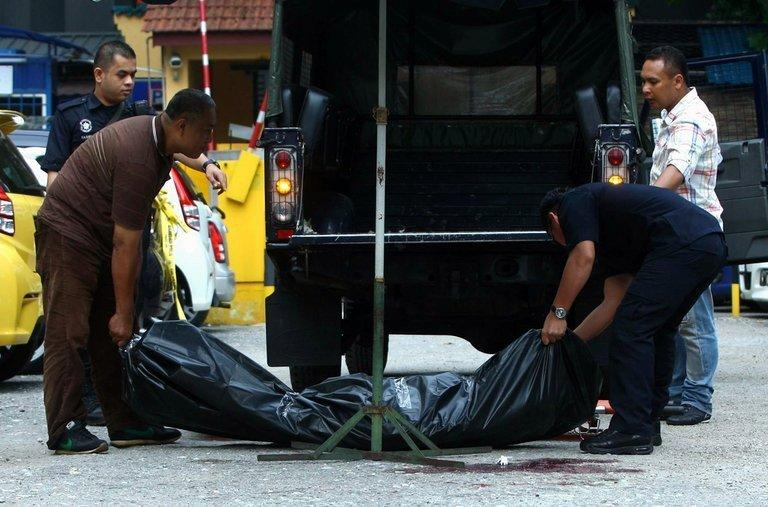 Police move the body of Hussain Ahmad Najadi after he was shot dead in a parking lot in Kuala Lumpur, July 29, 2013