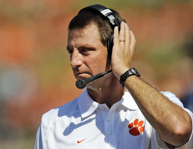FILE - In this Sept. 7, 2013, file phot, Clemson coach Dabo Swinney talks on the headphones during the second half of an NCAA college football game Saturday against South Carolina State at Memorial Stadium in Clemson, S.C. Swinney received a new, eight-year contract and a raise that increased his total pay for next season to $3.15 million. (AP Photo/ Richard Shiro, File)