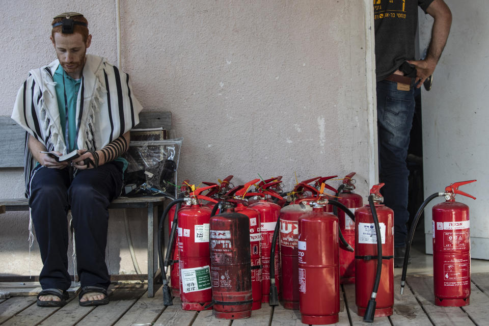 A Jewish student prays in the synagogue of the Maoz Military Preparation Program after it was damaged by fire during overnight clashes in the mixed Jewish-Arab city of Lod, Israel, Friday, May 14, 2021. (AP Photo/Heidi Levine)