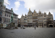 A woman runs though the nearly empty historic center of Antwerp, Belgium, Saturday, March 14, 2020. Belgium has closed schools, restaurants and bars, as as well as cancelled sporting and cultural events in an effort to contain the spread of the coronavirus. For most people, the new coronavirus causes only mild or moderate symptoms, such as fever and cough. For some, especially older adults and people with existing health problems, it can cause more severe illness, including pneumonia. (AP Photo/Virginia Mayo)