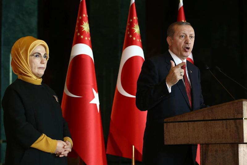 Turkish President Recep Tayyip Erdogan delivers a speech, flanked by his wife Emine, at the Presidential Palace in Ankara on February 9, 2016