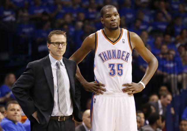 Oklahoma City Thunder head coach Scott Brooks, left, and forward Kevin Durant, right, watch during a foul shot by the Los Angeles Clippers in the third quarter of Game 1 of the Western Conference semifinal NBA basketball playoff series in Oklahoma City, Monday, May 5, 2014. Los Angeles won 122-105. (AP Photo/Sue Ogrocki)