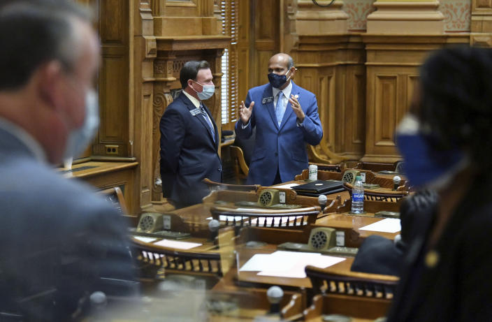 """FILE - In this Tuesday, Jan. 12, 2021, file photo, State Sens. Clint Dixon, rear left, and Sheikh Rahman, D-Lawrenceville, confer inside the Senate Chambers during the second day of the 2021 legislative session at the Georgia State Capitol, in Atlanta. Dixon, who represents a competitive district in the Atlanta suburbs, says he is disappointed that some conservative bills didn't pass in the 2021 General Assembly, but added """"there is a balance you've got to strike."""" (Hyosub Shin/Atlanta Journal-Constitution via AP, File)"""