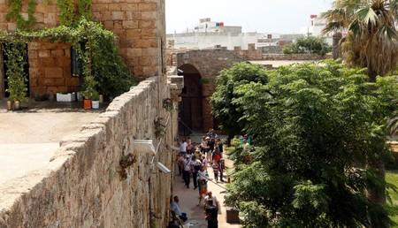 People walk together as they visit the citadel of Arwad, in the island of Arwad