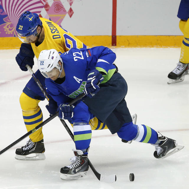 Sweden forward Daniel Sedin and Slovenia forward Marcel Rodman battle for the puck in the second period of a men's quarterfinal ice hockey game at the 2014 Winter Olympics, Wednesday, Feb. 19, 2014, in Sochi, Russia. (AP Photo/Mark Humphrey)