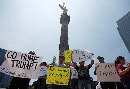 Demonstrators hold placards during a protest against the visit of U.S. Republican presidential candidate Donald Trump, at the Angel of Independence monument in Mexico City, Mexico, August 31, 2016. REUTERS/Tomas Bravo