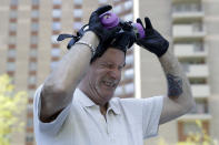 Safety Director Tony Barzelatto reacts as he pulls off his protective mask after disinfecting parts of a building in Co-op City in the Bronx borough of New York, Wednesday, May 13, 2020. Regular cleanings occur throughout the common areas of the buildings while the heavy disinfecting occurs in response to specific incidents, in this case reports of two coronavirus cases on the same floor. Within the Bronx, almost no place has been hit as hard as Co-op City. (AP Photo/Seth Wenig)