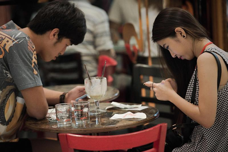 File photo shows a couple reading texts on their smartphones while having drinks together at a shopping mall in Bangkok (AFP Photo/Nicolas Asfouri)
