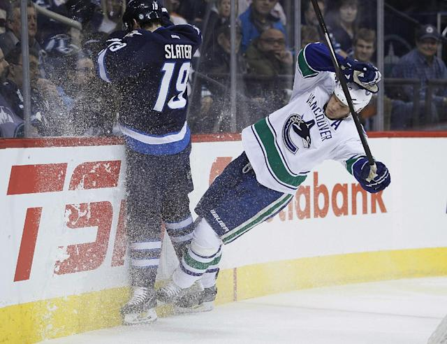 Vancouver Canucks' Kevin Bieksa (3) and Winnipeg Jets' Jim Slater (19) collide behind the Canucks' net during the second period of an NHL hockey game Wednesday, March 12, 2014, in Winnipeg, Manitoba. (AP Photo/The Canadian Press, John Woods)