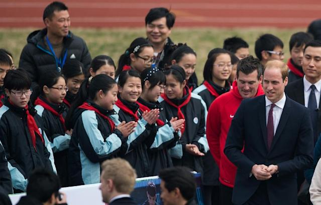 Britain's Prince William (C-R) talks to students during his visit to a football training camp in Shanghai, on March 3, 2015 (AFP Photo/Johannes Eisele)