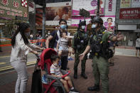 A family is diverted by police as a precaution during China's National Day in Causeway Bay, Hong Kong, on Thursday, Oct. 1, 2020. The popular shopping district of Causeway Bay saw a heavy police presence on the Oct. 1, China National Day holiday despite a low protester turnout. (AP Photo/Kin Cheung)