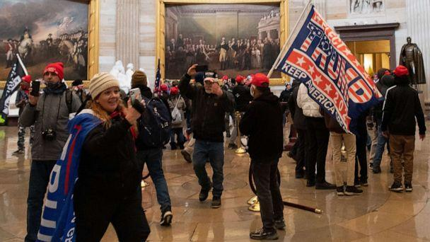 PHOTO: Jenny Cudd, in the hat and Trump flag cape, stands in the US Capitol's Rotunda along with other protesters on Jan. 6, 2021, in Washington, DC. (Saul Loeb/AFP via Getty Images)