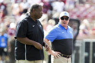 Kentucky head coach Mark Stoops talks with Kentucky associate head coach Vince Marrow during warmups prior to an NCAA college football game against Mississippi State, Saturday, Sept. 21, 2019, in Starkville, Miss. (AP Photo/Kelly Donoho)