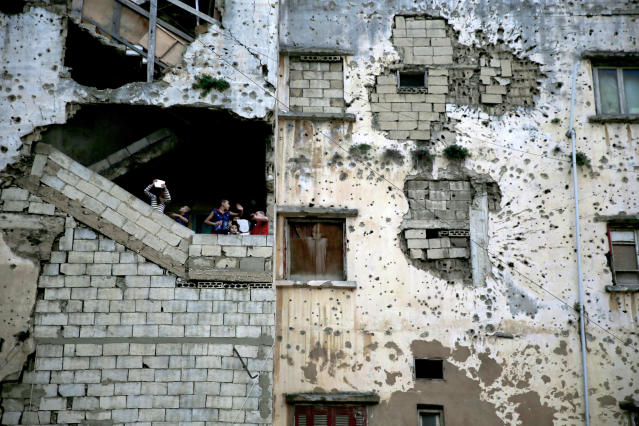 In this Nov. 28, 2015, photo, Syrian refugee children stand on the stairs of their apartment in a building damaged during Lebanon's 1975-1990 civil war on a former Beirut frontline, Lebanon. Nearly 30 years after civil war guns fell silent, dozens of bullet-scarred, shell-pocked buildings are still standing _ testimony to a brutal conflict that raged for 15 years and took the lives of 150,000 people.(AP Photo/Hassan Ammar)