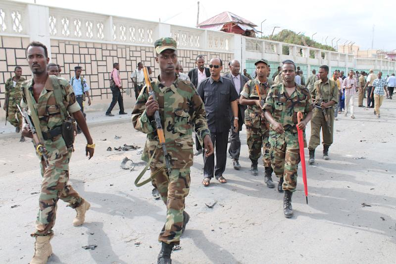 The Somali Defence Minister Abdihakin Haji Mohamud, centre, is surrounded by armed soldiers as he arrives at the scene where a suicide bomber detonated his explosives near a moving convoy of African union troops, in Mogadishu, Somalia, Friday, July,12 , 2013. Police have said that at least two people were killed and seven were injured in the blast. (AP Photo/Farah Abdi Warsameh)