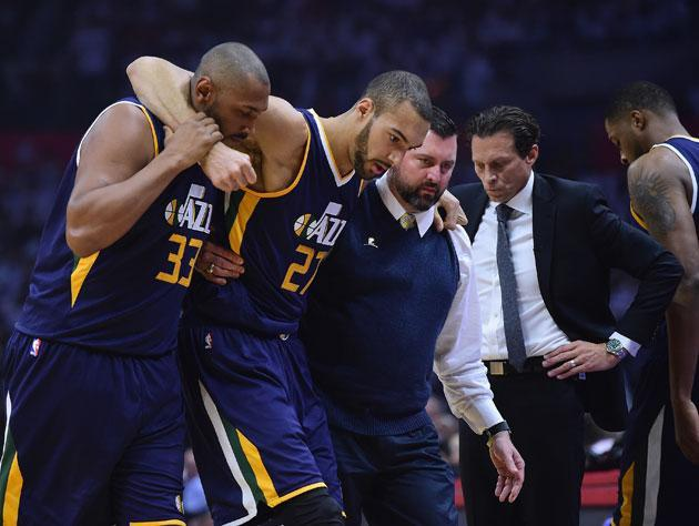 """<a class=""""link rapid-noclick-resp"""" href=""""/nba/players/5197/"""" data-ylk=""""slk:Rudy Gobert"""">Rudy Gobert</a> is helped off the court after injuring his knee in Game 1. (Getty)"""