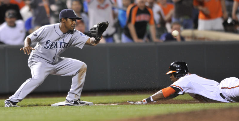 Seattle Mariners third baseman Chone Figgins awaits the throw as Baltimore Orioles Adam Jones slides into third for a triple in the fifth inning of a baseball game Wednesday, May 11, 2011 in Baltimore.(AP Photo/Gail Burton)