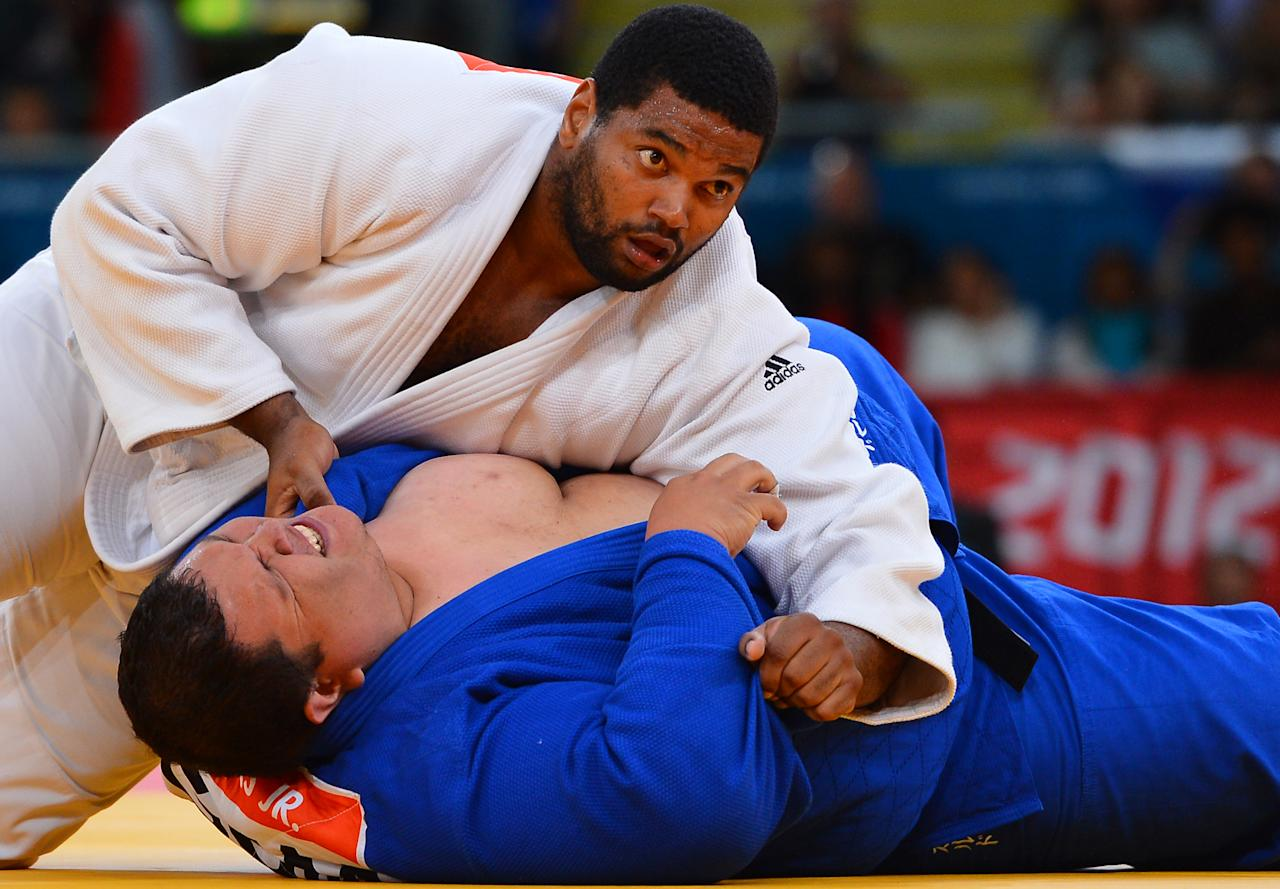 Cuba's Oscar Brayson (white) competes with Guam's Ricardo JR Blas (blue) during their men's  100kg judo contest match of the London 2012 Olympic Games on August 3, 2012 at the ExCel arena in London. AFP PHOTO / MIGUEL MEDINA