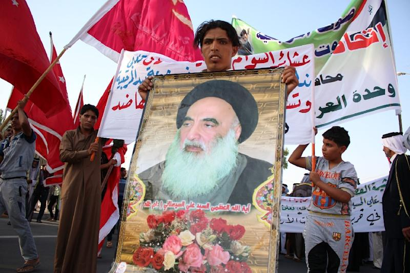 An Iraqi man holds a placard bearing a portrait of Shiite Muslim spiritual leader Grand Ayatollah Ali al-Sistani as people gather to show their willingness to join Iraqi security forces (AFP Photo/Haidar Mohammed Ali)