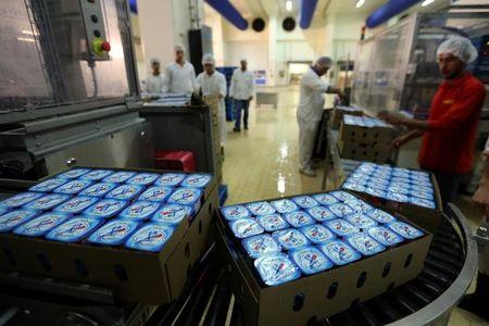 A worker carries the product of Juhayna Yoghurt at their factory in the outskirts of Cairo