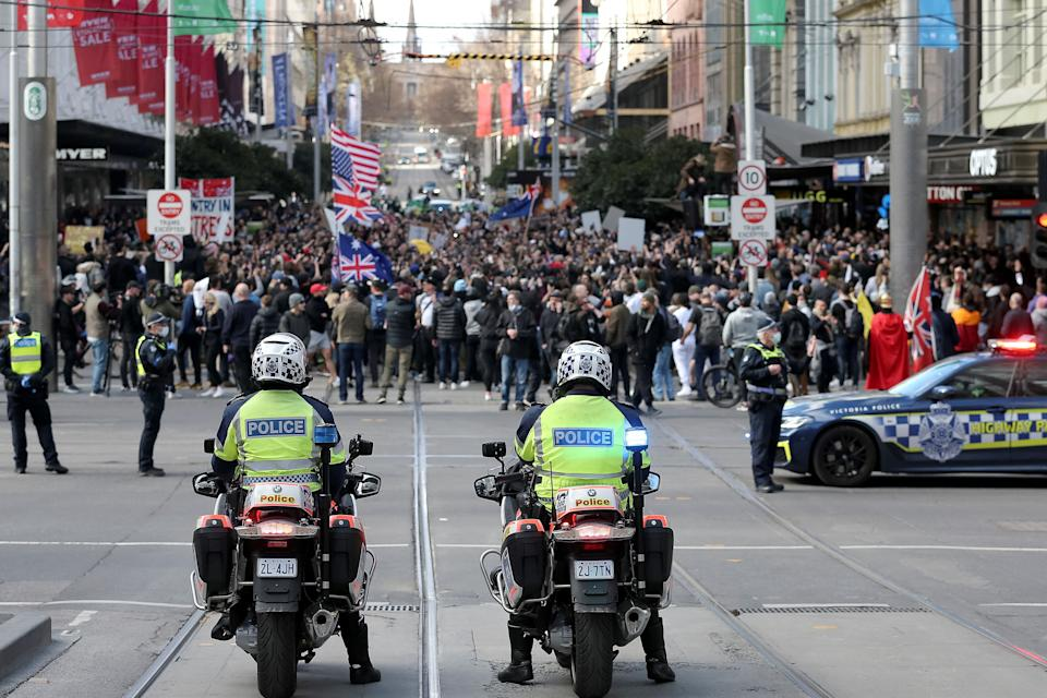 Police look on while protesters take part in a rally in Melbourne on July 24. Source: Getty
