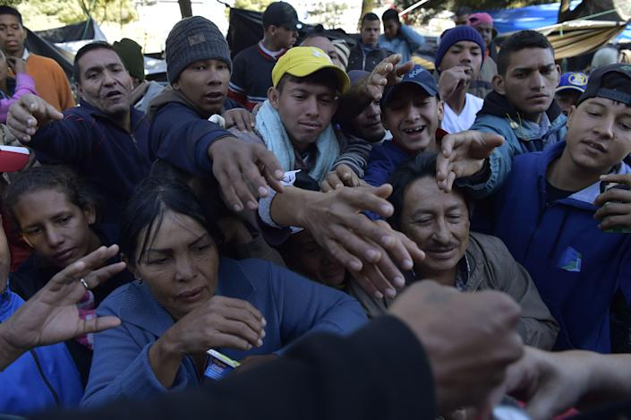 <p>Venezuelan citizens who remain in an improvised camp by the bus terminal in the north of Quito, Ecuador, reach for donations on Aug. 9, 2018. (Photo: Rodrigo Buendia/AFP/Getty Images) </p>