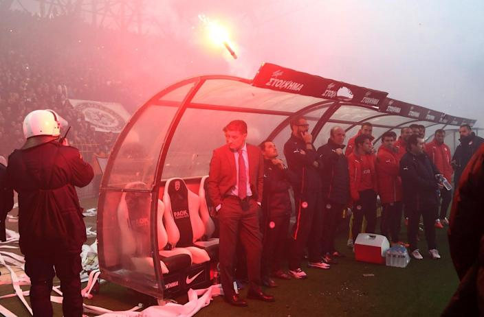 In this Wednesday, April 16, 2014 photo PAOK's fans throw a flare over the head of Olympiakos' coach Michel from Spain before a semi-final of the Greek Cup in the northern port city of Thessaloniki. Police in Thessaloniki have arrested a PAOK fan accused of dumping a crate of fish on the visiting Olympiakos bench, in a jibe that delayed a tense Greek cup semi-final for more than an hour. Another six PAOK supporters were arrested during clashes with police before and after Thursday's match, which PAOK won 1-0 to advance on aggregate. The game was repeatedly halted by on-turf brawls, resulting in three red cards, while PAOK fans in the stands lit thousands of flares, and several were thrown on the pitch. (AP Photo/InTime Sports, Yorgos Matthaios) GREECE OUT