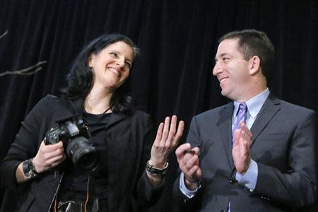 Poitras, and Greenwald smile as they receive the George Polk Awards in New York