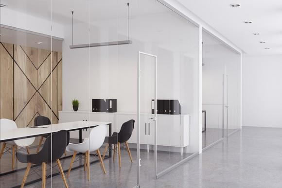 Side view of a glass-enclosed conference room filled with contemporary office furniture.
