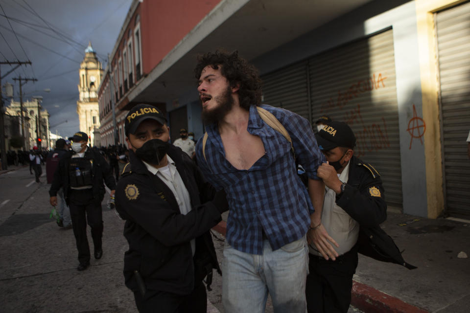 A man is detained by police near the Congress building after protesters set a part of the building on fire, in Guatemala City, Saturday, Nov. 21, 2020. Hundreds of protesters were protesting in various parts of the country Saturday against Guatemalan President Alejandro Giammattei and members of Congress for the approval of the 2021 budget that reduced funds for education, health and the fight for human rights. (AP Photo/Oliver De Ros)