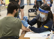 FILE - In this April 8, 2021, file photo, Kent State University student Jarrett Woo gets his Johnson & Johnson COVID-19 vaccination from Kent State nursing student Allie Rodriguez in Kent, Ohio. Even as restrictions relax across much of the United States, colleges and universities have taken new steps to police campus life as the virus spreads through students who are among the last adults to get access to vaccines. (AP Photo/Phil Long, File)