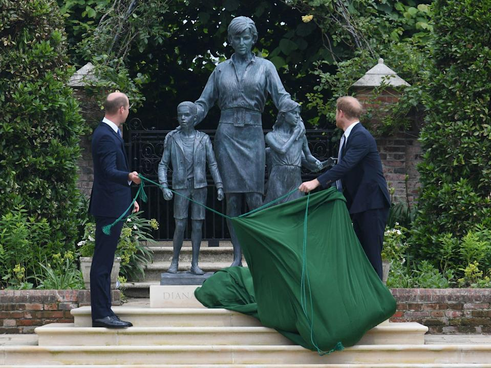 Prince Harry and Prince William pull back a covering to reveal the statue of their mother, Princess Diana, on what would have been her 60th birthday.