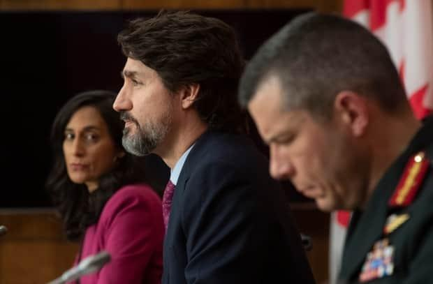 Public Services and Procurement Minister Anita Anand (left) and Major General Dany Fortin look on as Prime Minister Justin Trudeau responds to a question during a news conference in Ottawa Monday, Dec. 7, 2020.