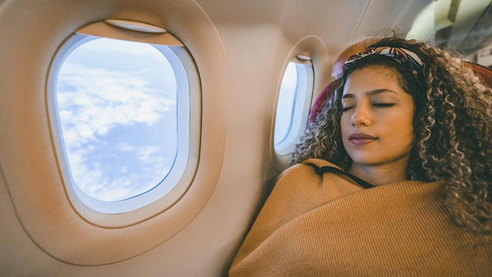 Portrait of a beautiful woman traveling by plane and sleeping during the flight - travel concepts.