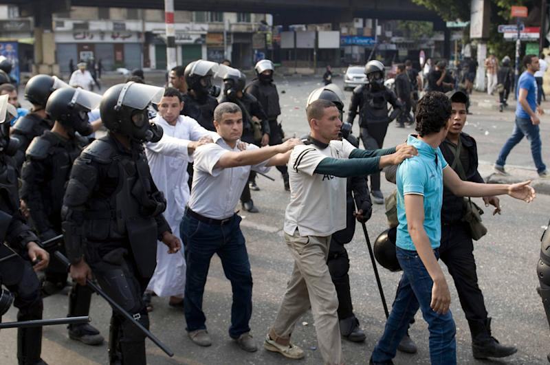 FILE -- In this Sunday, Oct. 6, 2013 file photo, supporters of ousted President Mohammed Morsi are detained during clashes with riot police in Cairo, Egypt. The trial of ousted President Mohammed Morsi is hardly the only one Egypt's new leaders plan against his Muslim Brotherhood. Authorities are preparing prosecutions against some 2,000 jailed Brotherhood members, on allegations ranging from inciting violence to terrorism, aiming to put much of its leadership behind bars for years. (AP Photo/Nameer Galal, File)