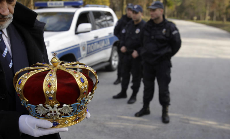 A man carries a crown of Peter II Karadjordjevic during a solemn ceremony after the remains of Yugoslavia's last king were flown back to Serbia in Belgrade, Serbia, Tuesday, Jan. 22, 2013. The former king fled the Nazi occupation of Yugoslavia at the start of World War II and never returned, as Communists took over at the end of the war. He died in exile and was buried at a Serbian Orthodox monastery in Libertyville, Illinois — the only European monarch buried on U.S. soil. (AP Photo/Darko Vojinovic)