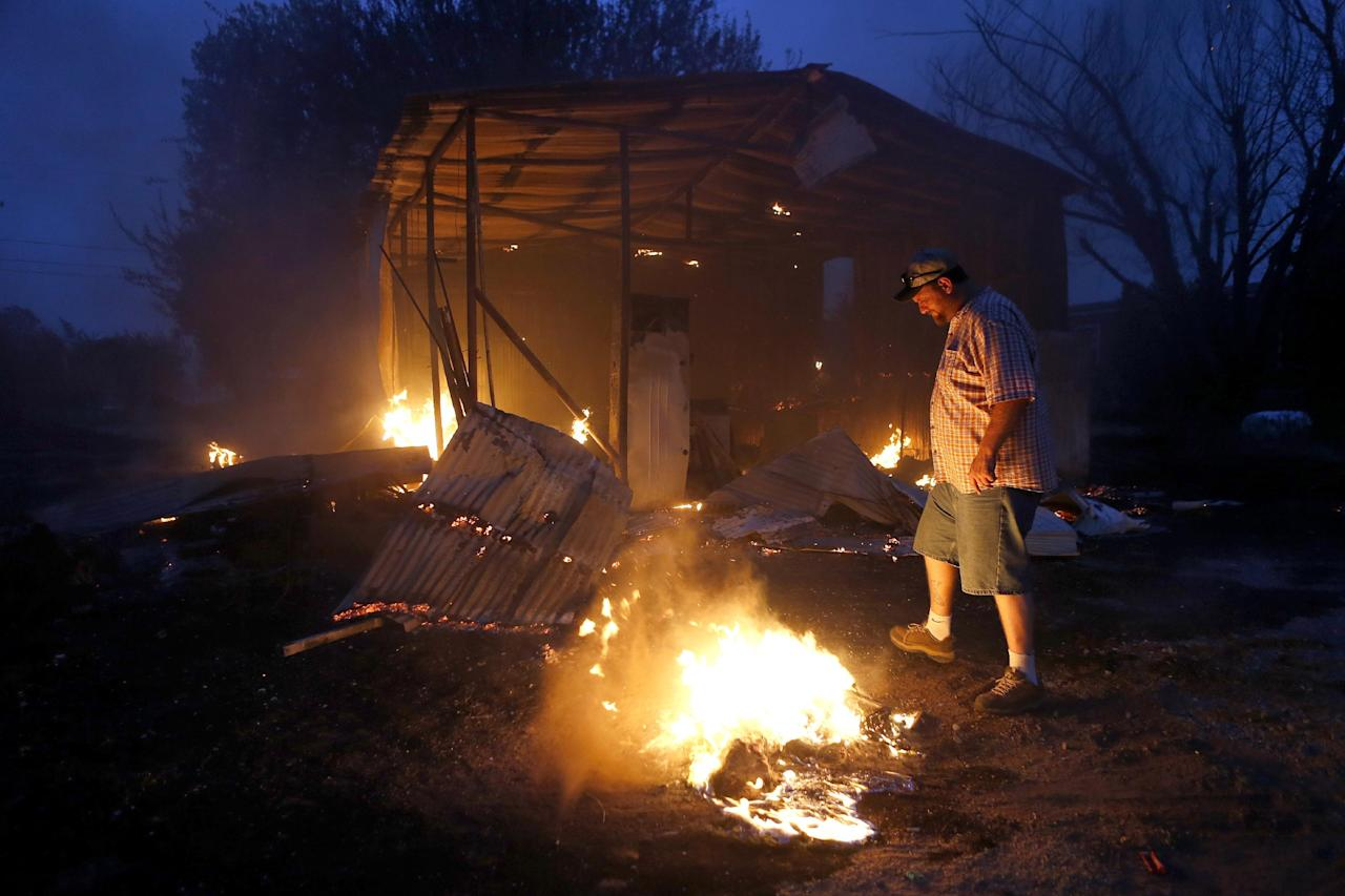 Phillip Green tries to put out hot spots near his burned storage building next to his home in Luther, Okla., after wildfire moved through the area on Friday, August 3, 2012. A wildfire whipped by gusty, southerly winds swept through rural woodlands north and south of Oklahoma City on Friday, burning several homes as firefighters struggled to contain it in 113-degree heat. (AP Photo/The Oklahoman, Bryan Terry)