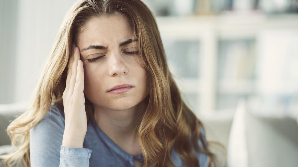 Young woman with headache in home interior