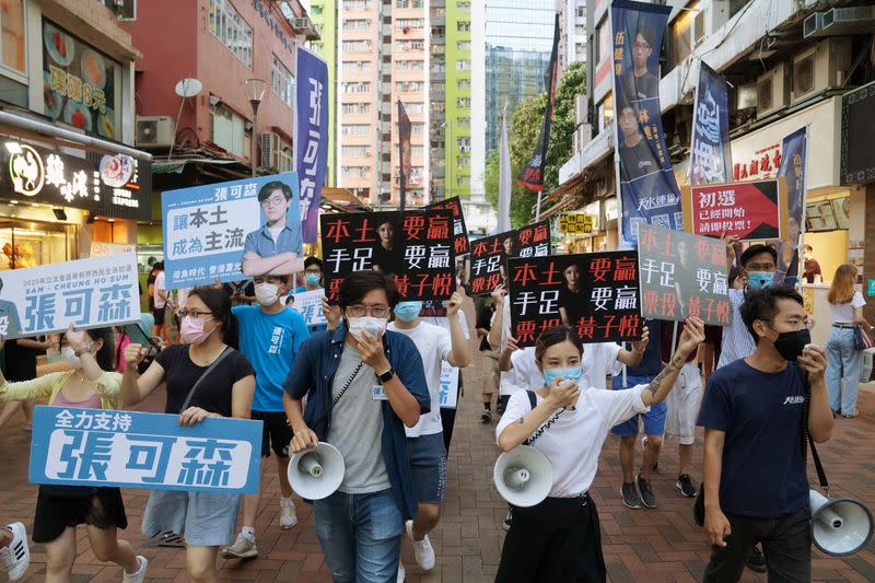 Sam Cheung Ho-sum and Wong Ji-yuet march on a street to campaign for the primary election in Hong Kong
