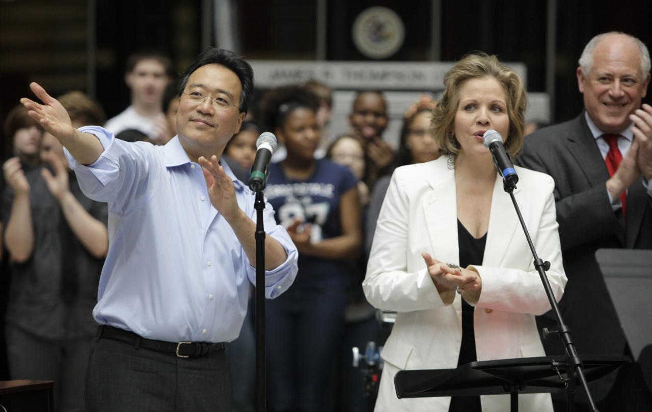 World-famous cellist Yo-Yo Ma, left, and famed soprano Renee Fleming speak as they performed with a choir of dozens of high school students in the rotunda of the State of Illinois building, the James R. Thompson Center, Monday, March 19, 2012, in Chicago. At right is Illinois Gov. Pat Quinn. The Monday afternoon performance was to promote the Chicago Symphony Orchestra's Citizen Musician initiative. The Lyric Opera of Chicago also sponsored the event and Illinois Gov. Pat Quinn attended. (AP Photo/Kiichiro Sato)