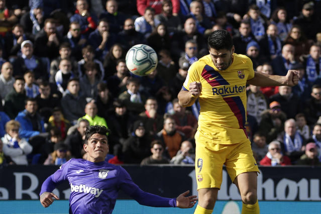 Barcelona's Luis Suarez, right, scores his side's opening goal during a Spanish La Liga soccer match between Leganes and FC Barcelona at the Butarque stadium in Madrid, Spain, Saturday Nov. 23, 2019. (AP Photo/Paul White)