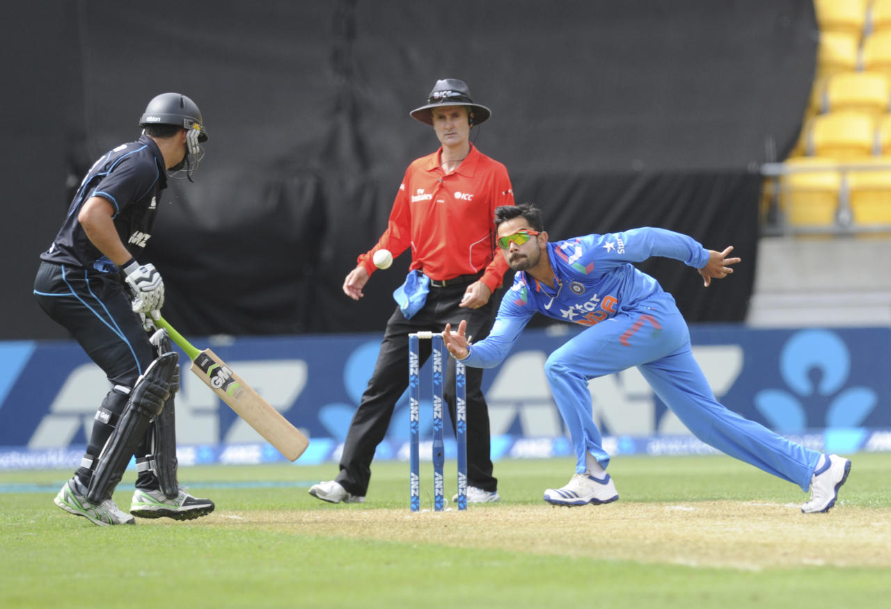 India's Virat Kohli, right, fields off his own bowling in front of New Zealand's Ross Taylor in the fifth and final one-day international cricket match in Wellington, New Zealand, Friday, Jan. 31, 2014. (AP Photo/SNPA, Ross Setford) NEW ZEALAND OUT