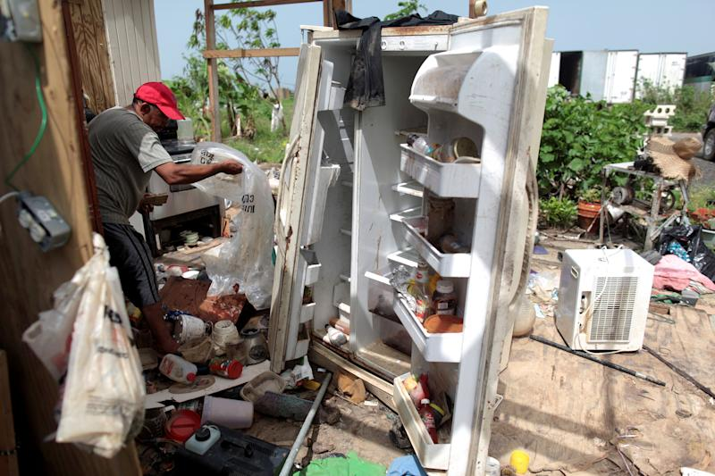 FILE PHOTO: Jose Taveras sorts things in the remains of his home, after the island was hit by Hurricane Maria in September, in Toa Alta, Puerto Rico October 19, 2017. REUTERS/Alvin Baez/File Photo