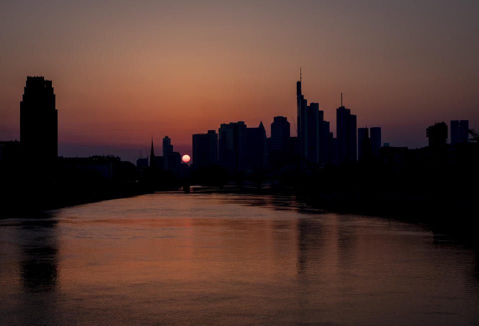 The sun sets behind the buildings of the banking district in Frankfurt, Germany, Saturday, March 28, 2020. Due to the coronavirus the economy expects heavy losses worldwide. For most people, the new coronavirus causes only mild or moderate symptoms, such as fever and cough. For some, especially older adults and people with existing health problems, it can cause more severe illness, including pneumonia.(AP Photo/Michael Probst)